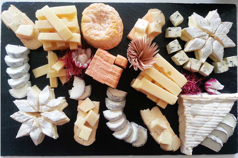 Cheese platter with about 6 size different cheese types cut up in creative ways