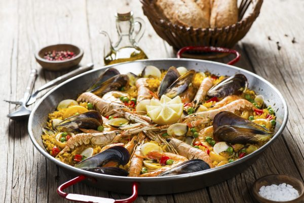 Closeup of paella with seafood on a wooden table.